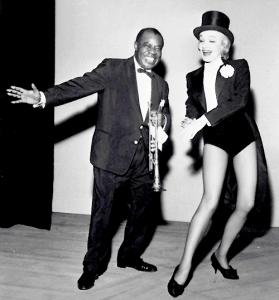 Marlene Dietrich muove qualche passo di danza con il grande Sachmo, Louis Armstrong.