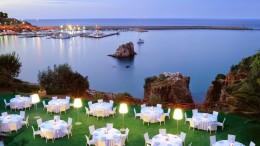 Un'immagine serale di Presidiana porto: sullo sfondo a sx l'Ormeggio Eolo. In primo piano una terrazza dell'Hotel Le Calette con piscina, stanze e suites sul mare