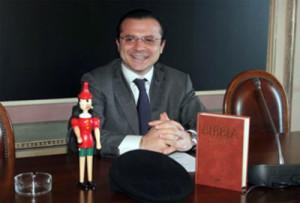 Cateno De Luca fattosi ritrarre qui fra la Bibbia e Pinocchio in una spiritopsa immagine, studia da sindaco di Messina e appoggia vigorosamente Musumeci