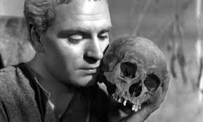 Laurence Olvier in Amleto accosta alla guancia il teschio dell'amico Yorick, riflettendo sulla caducità delle vita: la finzione è meramente poetica. Yorick non poteva essere già un teschio. Ma Shakespeare giganteggia. Il grande monologo verrà nell'atto seguente...