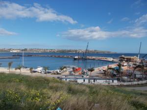 Si lavora nei primi giorni del 2018. A dx la struttura riconoscibile della club house, sul mare il grande pontone che sta affrettando la rifinitura dei moli, delle banchine e dei pontili in muratura.