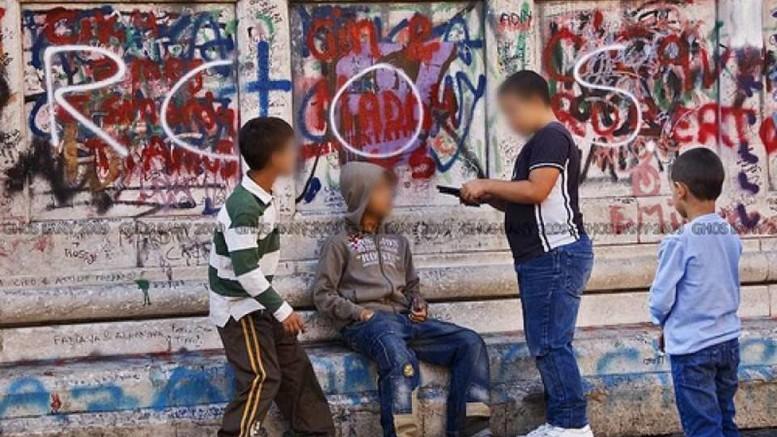 """""""Scugnizzi"""" traviati a Napoli. I segni che imbrattano i muri, a volte osceni, a volte artistici, sono il segno della carenza di spazi d'espressione.  Nei telefonini e nell'ipad spesso i ragazzi trovano un mondo in miniatura che surroga quello reale che probabilmente sceglierebbero se """"esistesse"""" alla loro portata.  Nella violenza credono, forse, di vivere un attimo eroico, un raro momento di concretezza e realtà... (Direttore)"""