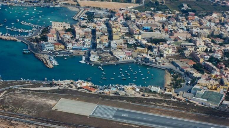 Il porto naturale di Lampedusa e in basso la pista dell'aeroporto, la cui vicinanza non contamina l'immagine tradizionale dei luoghi (per quanto da questa immagine presa dall'alto possa sembrare incredibile).