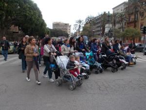 """Mamme con bimbi alla partenza dalle """"Croci"""". Oltre alle carrozzelle """"piene"""", una vuota simbolo dei bambini mai nati."""