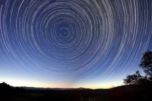 """Un'immagine suggestiva e simbolica:il cielo ruota attorno alla stella polare con la """"camera"""" ad obiettivo aperto per tutta la notte. L'effetto è dovuto alla roitazione terrestre,mapuò essere un simbolo: non esiste unalinea retta e nullasta fermo nell'universo. A capirolo hanno contribuito Archimede, Galilei, Newton, Einstein..."""