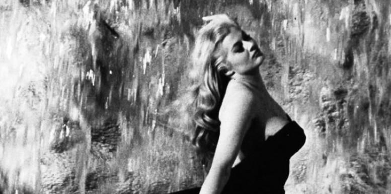 """Anita sta per chiamare """"Marcello, Marcello!"""" nella Dolce vita. Mastroianni entrerà anche lui nella fontana di Trevi e la bacerà. Ambedue con i vesti ti indosso."""