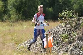 Orinteering di alto livello: l'atleta corre in cross country. Ha in tasca bussola e cartina e compasso.