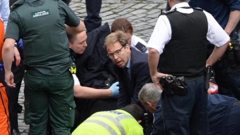 Giacca e cravatta, con la camicia e le mani sporche di sangue, la sua figura spicca tra quelle dei soccorritori nelle foto pubblicate dai media britannici, mentre in ginocchio pratica la respirazione bocca a bocca al poliziotto ferito dagli islamici  e cerca di arrestare l'emorragia... E' il deputato della Afd, T. Hellwood...