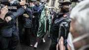 Silvia Romano, escorted by Carabinieri, arrives at her home wearing a surgical mask to guard against COVID-19, in Milan, Italy, Monday, May 11, 2020. The young Italian woman has returned to her homeland after 18 months as a hostage in eastern Africa. (AP Photo/Luca Bruno)