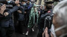 La grottesca 'mise' di Silvia Romano, scortata dai Carabinieri arriva a casa propria.