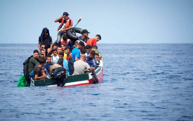 Non sempre i 'barchini' sono tanto carichi e il viaggio è così scomodo: dalla Tunisia sbarcano sorridendo e salutano allegramente i bagnanti esivi. Sono i due tipi di turismo a Lampedusa...